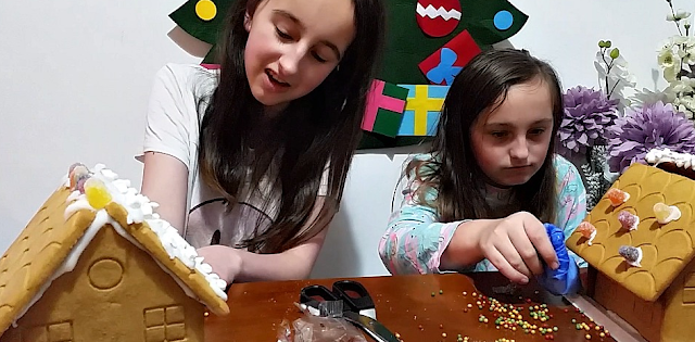 my girls making a gingerbread house
