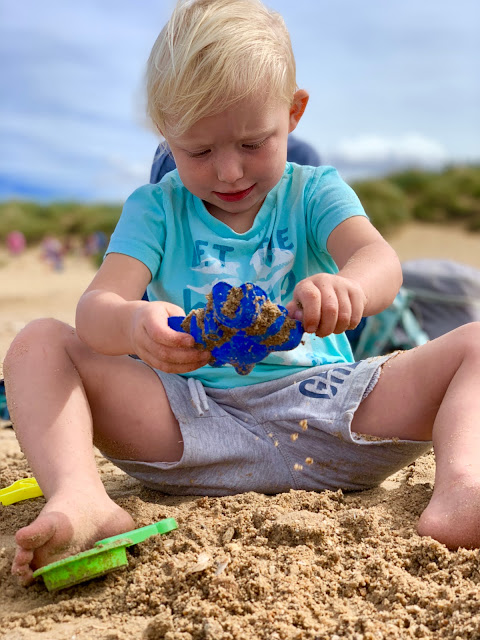 3 year old playing with sand and a blue plastic crab