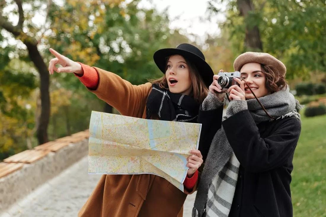 Duas meninas felizes com um mapa e uma camera na mao