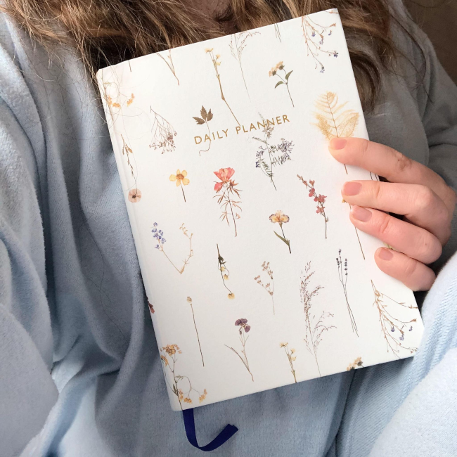 Girl holding a diary up against her torso, wearing pale blue pajamas