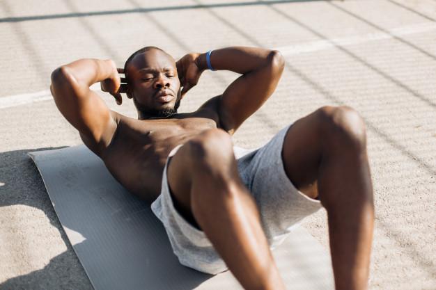 homem negro sem camisa fazendo exercício abdominal em casa