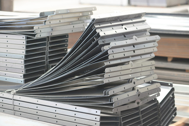 piles of formed metal parts made from sheet metal