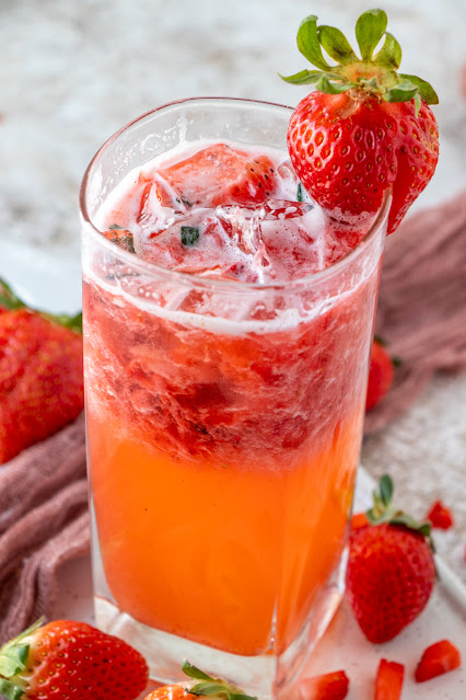Cocktail in glass with strawberry garnish