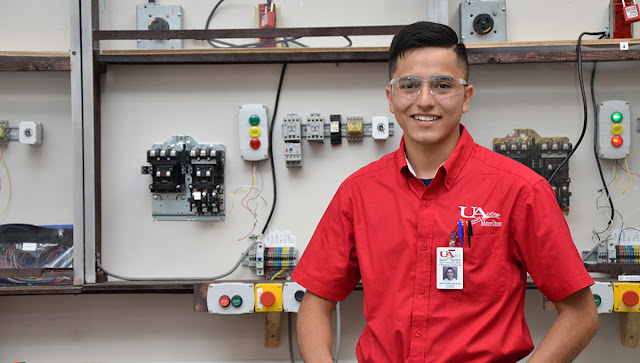 male student standing in front of equipment