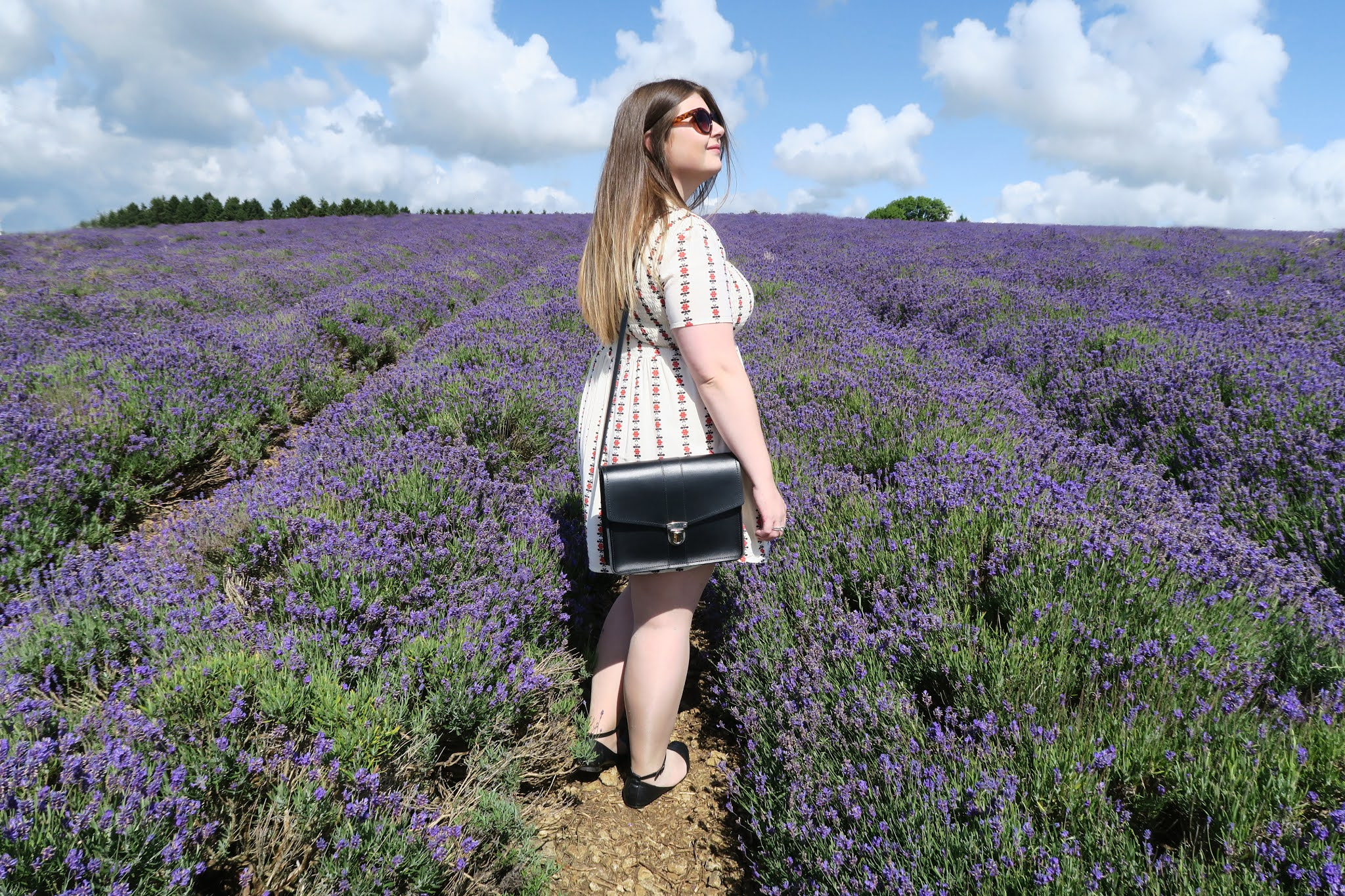 Grace is wearing a short white dress. She is standing in a field full of cotswold lavender