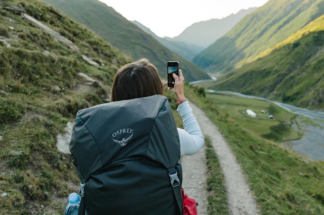 Woman with backpack taking a photo with her phone