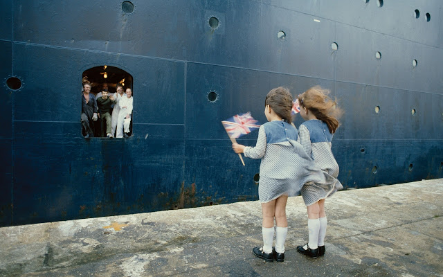 Two girls wave small flags as British soldiers leave for the Falkland Islands. 1982