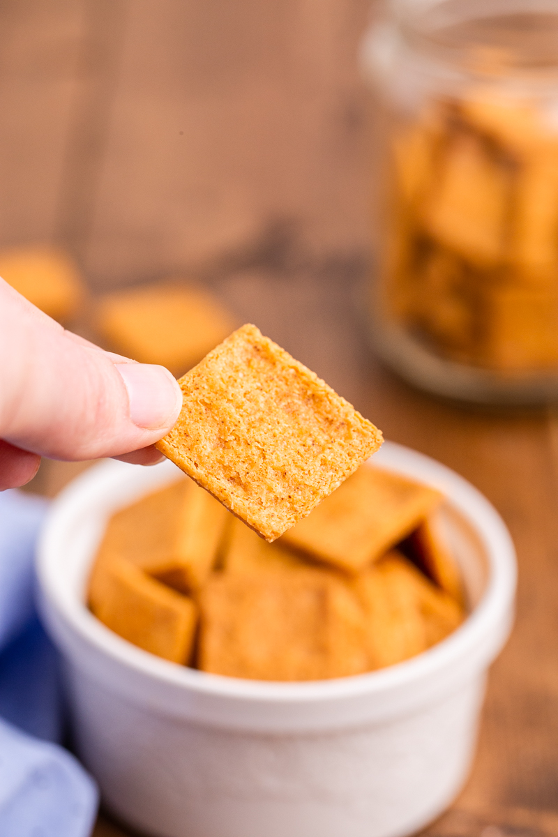 Closeup photo of someone holding a Keto Smoked Cheddar Cracker (Cheez-Its) in their hand with a small white bowl full of them behind their hand.