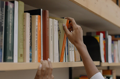 A person's hand pulling a book off of a bookshelf.