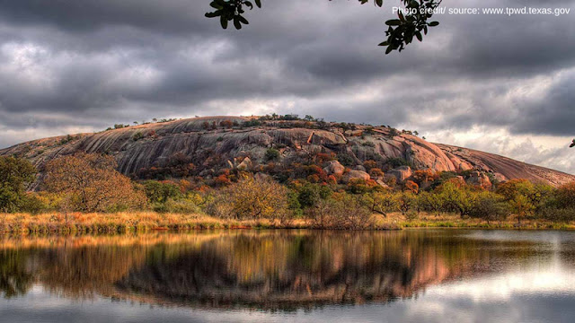 the reflection of Enchanted Rock in nearby waters on an overcast day
