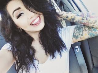 Simpática mujer tatuada , está en su coche, rie mordiendose la lengua