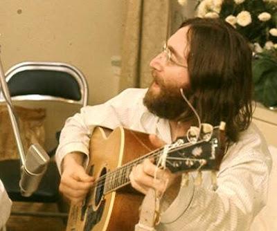 Foto de John Lennon cantando con su guitarra