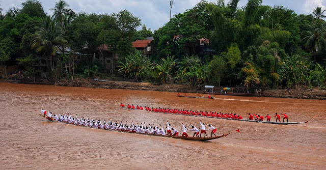 two boat racing teams race down the river in Luang Prabang