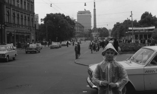 """1970-е годы. Рига. Улица Ленина. Строящаяся гостиница """"Латвия"""", монумент Свободы и часы в новом оформлении... Девочка в модном дождевики"""