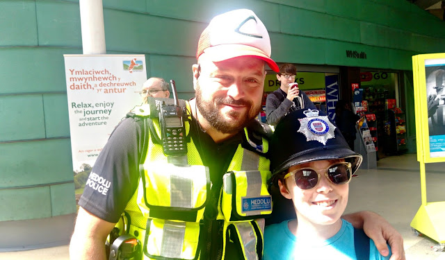 A boy and a policeman with their hats swapped.