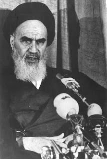 Newspaper photo of Ayatollah Khomeini speaking at microphones