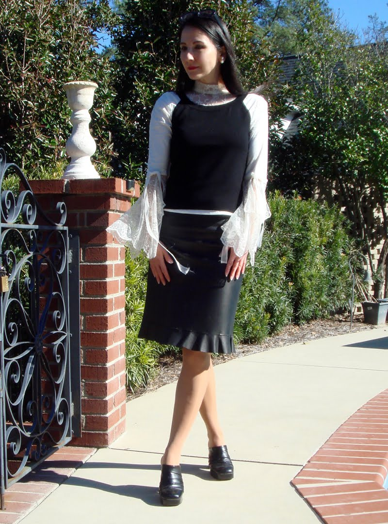Wearing blouse with flared lace sleeves and lace collar, topped with a black sleeveless sweater. Black leather skirt with ruffled trim and black clogs. Black sunglasses on head.