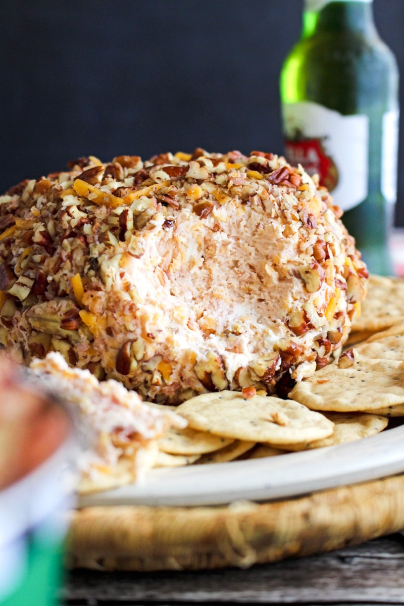 Side view of a Ham and Cheddar Cheese Ball on a plate surrounded by crackers on a wood background.