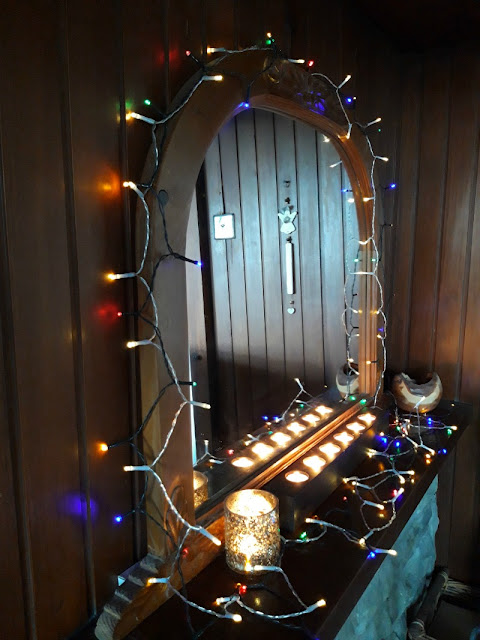 A photo of a mirror in curved wooden frame decorated with multi coloured fairy lights and with candles glowing next to it