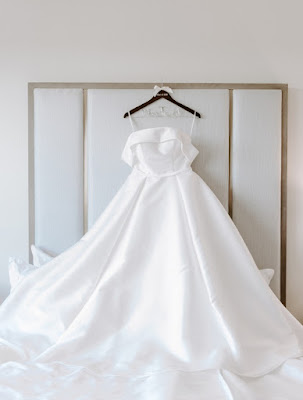 hanging wedding dress on bed