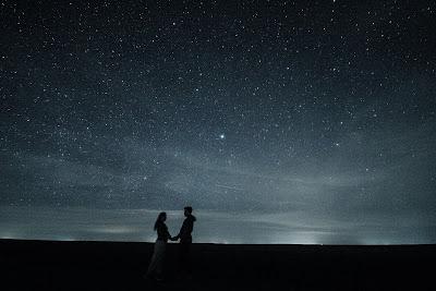 Una coppia si abbraccia sotto un cielo stellato
