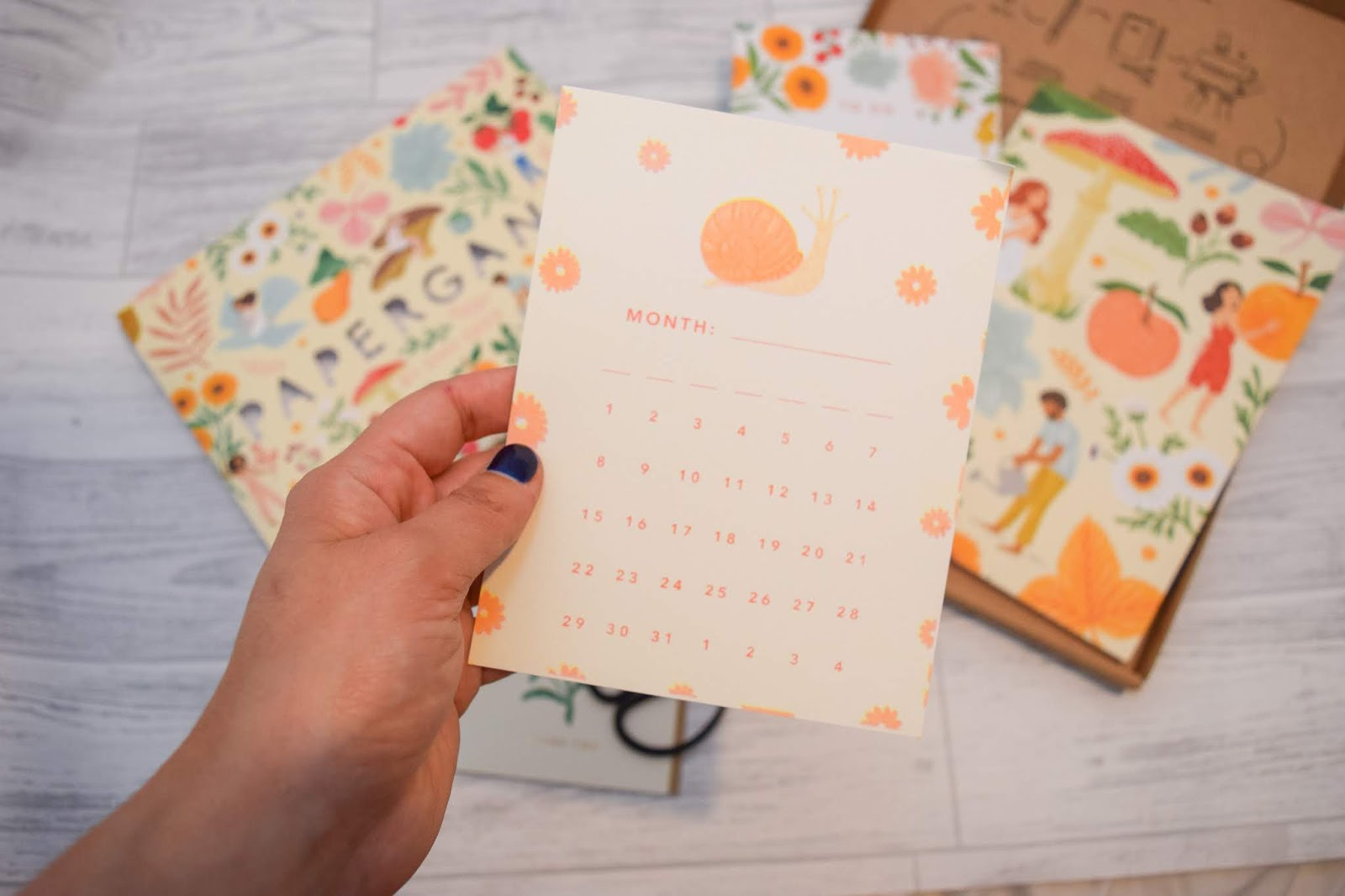 A hand holding a piece of card with a picture of an orange snail, numbers up to 31 and spaces to fill in the days of the week and the month.