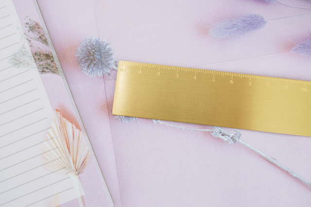 Gold ruler on a lilac wrapping paper