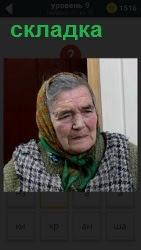 Пожилая женщина со складками на лице и платке, одета в клетчатую жилетку с серьезным выражением лица