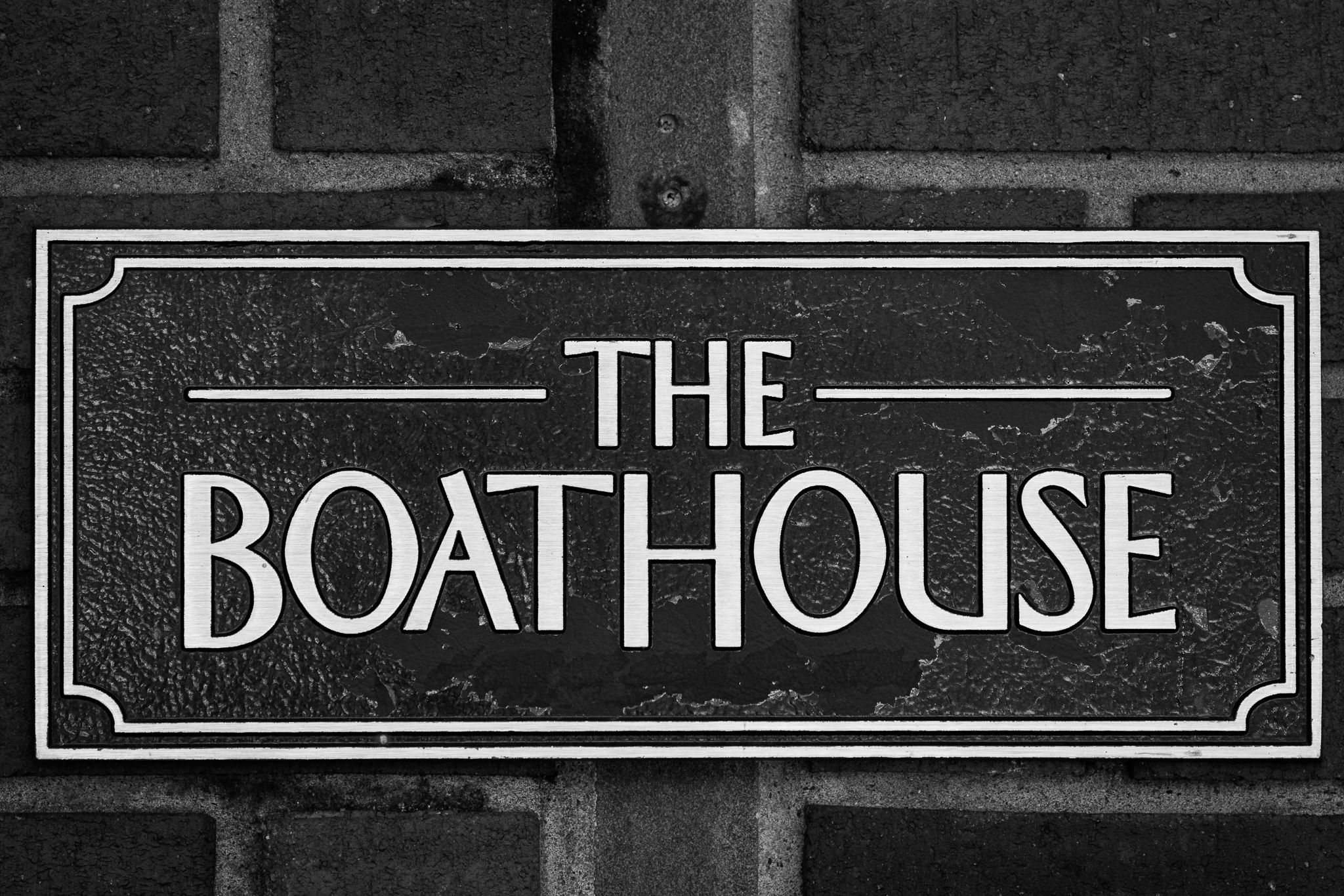 a black and white photograph of the sign at the boathouse restaurant in central park