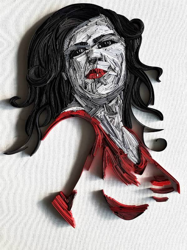 quilled paper portrait of dark-haired woman with red lips and dress