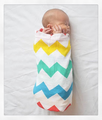 A baby wrapped in a rainbow chevron swaddle