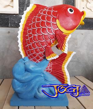 Patung air mancur bentuk Ikan hias yang dibuat dari batu alam putih atau batu alam paras jogja yang di cat merah