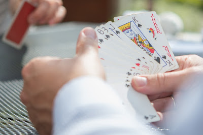 A picture of a person holding cards for gamble game.