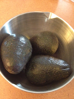 Three avocados in a stainless steel bowl