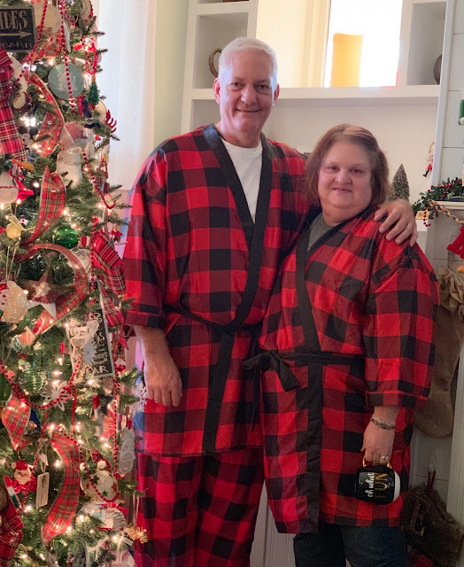 Christmas tree, man and woman wearing matching buffalo plaid pajamas.