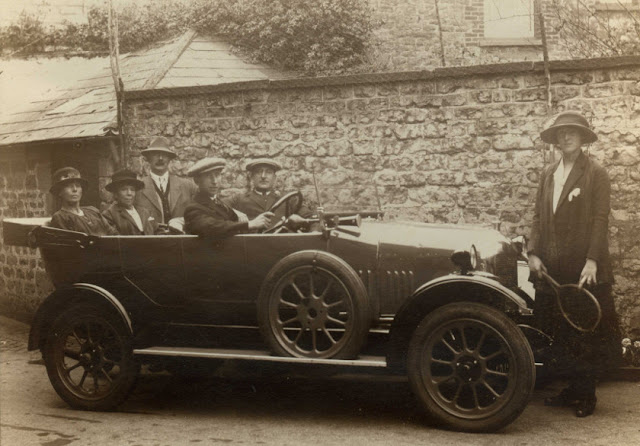 Car with 5 passengers and one young girl standing