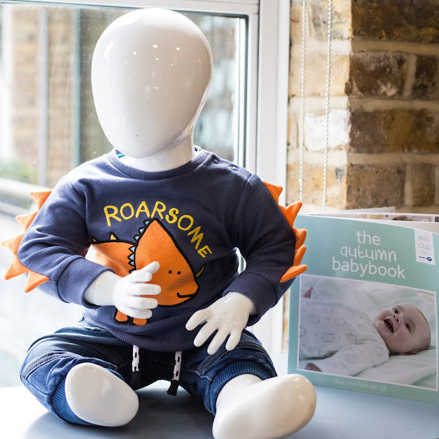"A mannequin wearing a sweatshirt with scales on the arms, a dinosaur on the front and the word ""Roarsome"""