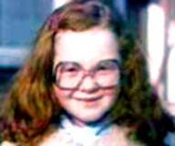 Ann Gotlib | A young girl with red hair is wearing large square glasses smiling | True Crime | mommalovestruecrime.com