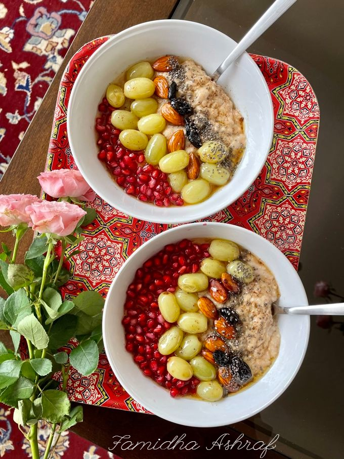 two bowl of oatmeal topped with roasted grapes and nuts