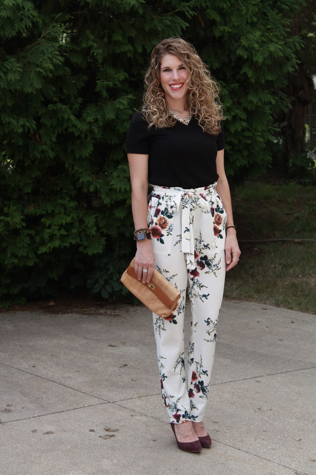 white floral paper bag pants, black tee, straw clutch, burgundy heels