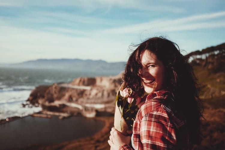 como ser uma pessoa melhor - mulher com uma blusa xadrez vermelha sorrindo, segurando flores numa praia que tem pedras- vento está forte e movimenta os cabelos dela.