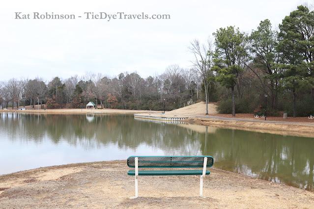 A bench alongside a pond at Olive Branch City Park in Olive Branch, MS.