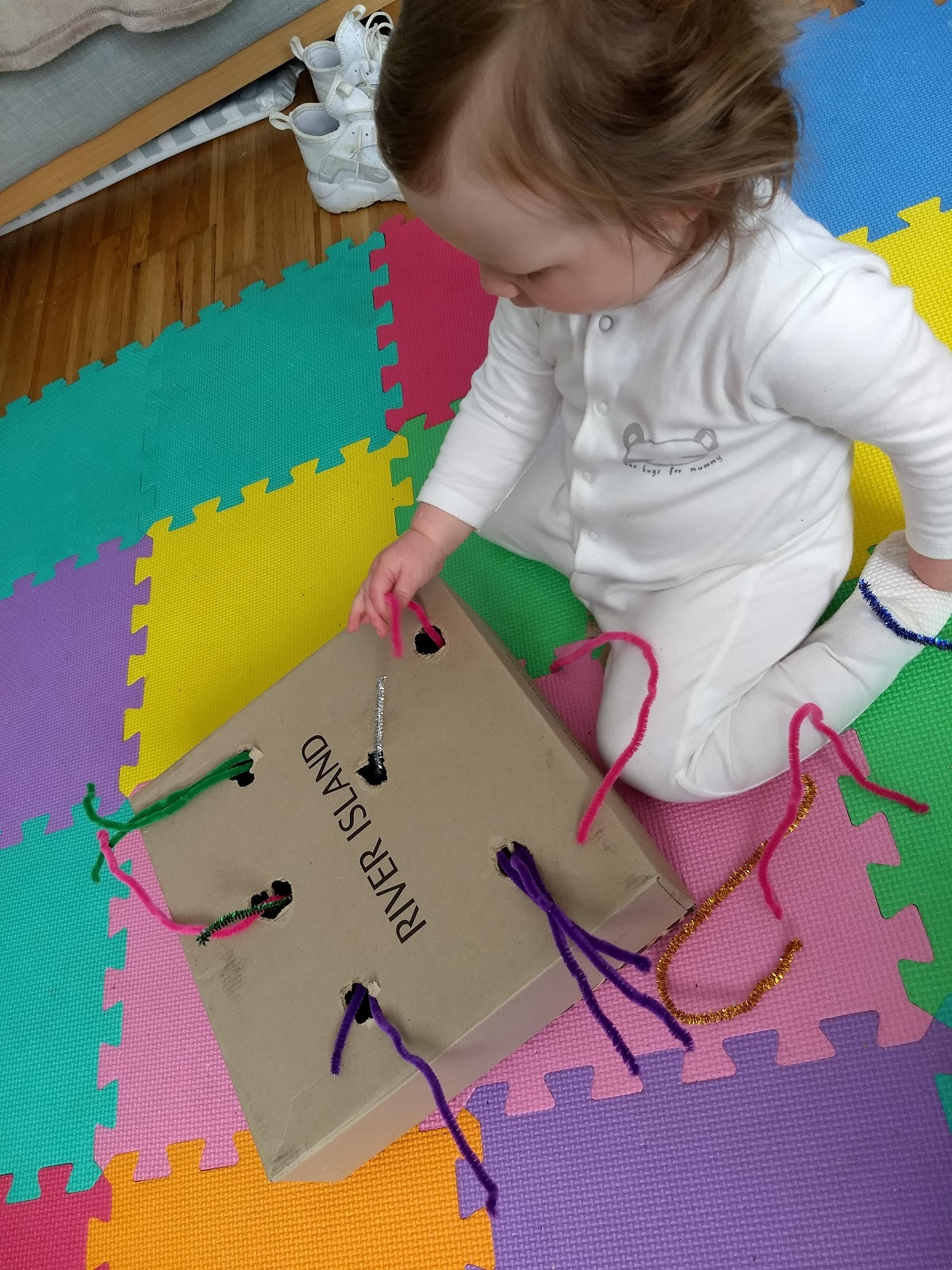 Toddler indoor play, holes in a shoebox.