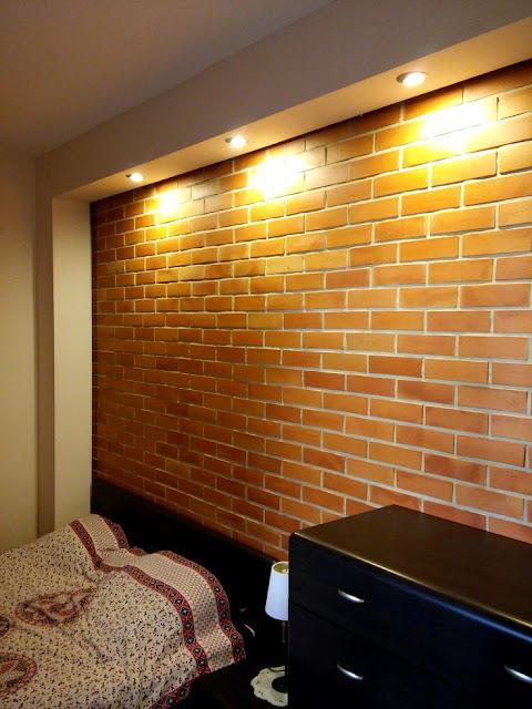 Ceglana ściana w sypialni. Barwa cegieł wyeksponowana jest dzięki kinkietom w podwieszanym suficie.