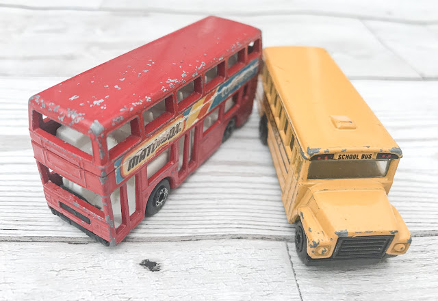A toy yellow american school bus and a red doubledecker bus