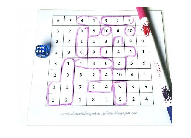 na zdjęciu plansza do gry z zakreślonymi już polami, po lewej stronie leży niebieska kostka do gry a po prawej różowy pisak