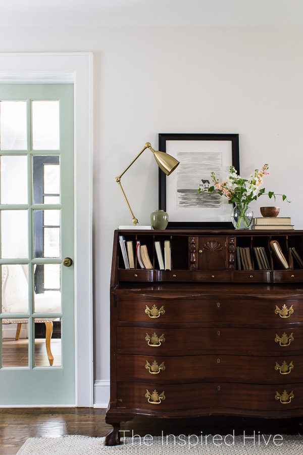 Sage green french door with brass knob next to antique secretary desk