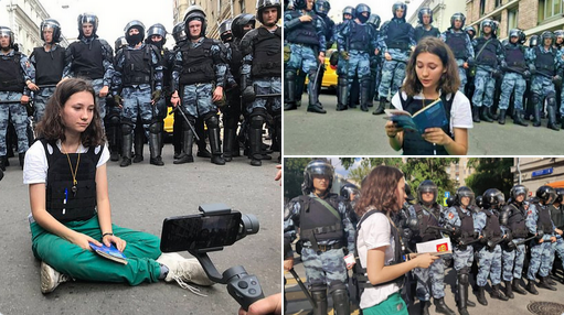 Teenage-girl-sits-in-front-of-police-read-constitution-during-Russian-Protests