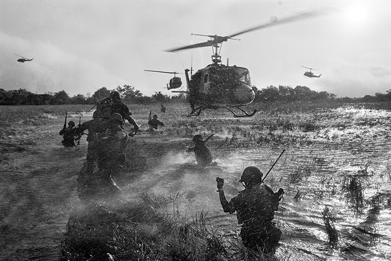 As u s eagle flight helicopters hover overhead south vietnamese troops wade through a rice paddy in long an province during operations against viet cong