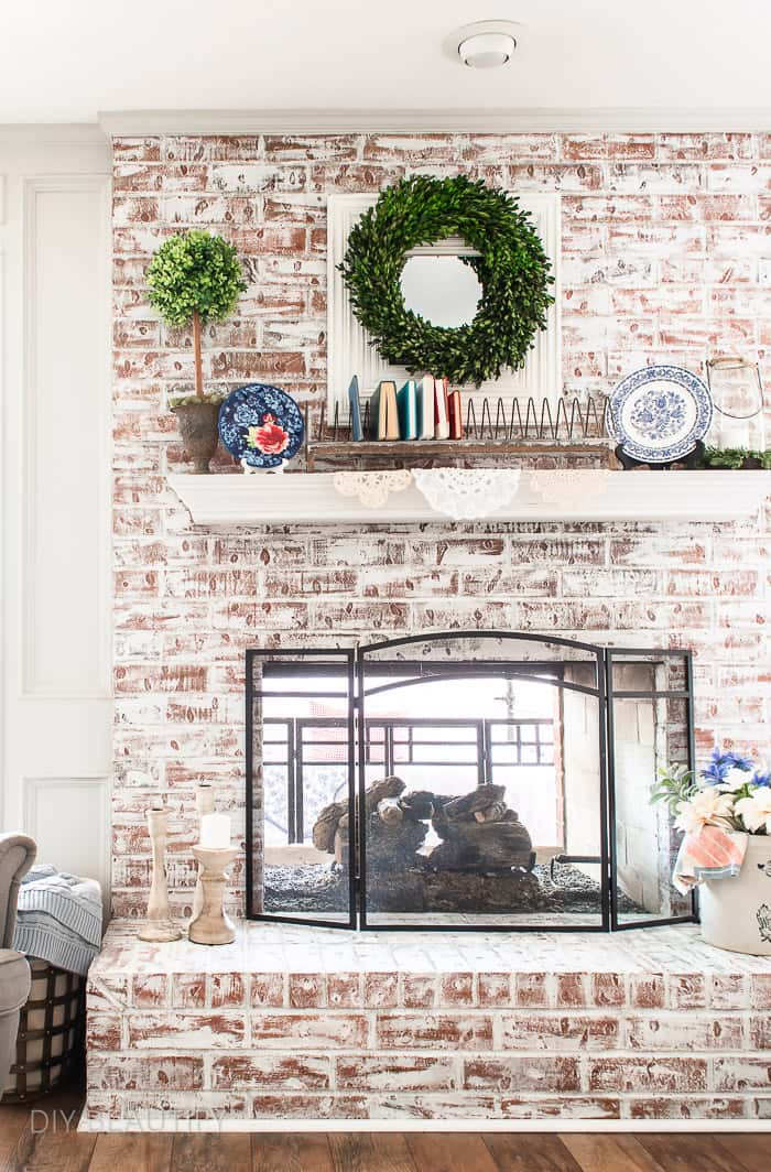 chalk painted brick fireplace decorated with patriotic cottage charm